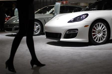 A model walks by Porsche vehicles at the New York International Auto Show in New York City, April 21, 2011. REUTERS/Mike Segar