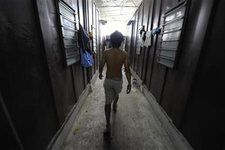 A foreign worker from Nepal walks along the corridor in between cargo containers where he and his colleagues live, in Meru outside Kuala Lumpur June 25, 2010. REUTERS/Samsul Said