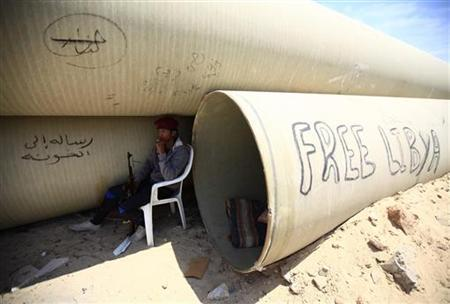 A rebel fighter sits at checkpoint on the road from the Libyan rebel-held city of Misrata to the western frontline, where rebels trying to advance on the capital Tripoli are fighting forces loyal to Muammar Gaddafi, June 21, 2011. REUTERS/Zohra Bensemra