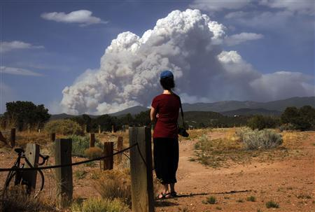 A woman looks at smoke from the Pacheco Canyon Wildfire near Santa Fe, New Mexico June 19, 2011. REUTERS/Brian Snyder