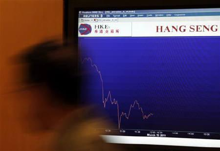 A floor trader walks past a panel displaying the blue-chip Hang Seng index trend at the end of the morning trading at the Hong Kong Stock Exchange March 15, 2011. REUTERS/Bobby Yip/Files