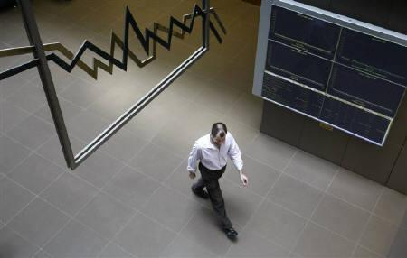 An employee walks inside the Athens' stock exchange in Athens April 12, 2010.  REUTERS/John Kolesidis/Files
