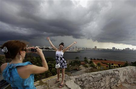 A tourist poses for a picture at colonial-era fortress 'El Morro' with Havana in the background as storm clouds gather in the sky May 24, 2011. REUTERS/Desmond Boylan