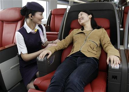 A train attendant (L) helps a passenger to adjust her seat at the business class carriage on a CRH 380A bullet train travelling on the newly built high-speed railway between Shanghai and Beijing during a test ride departed from Shanghai June 16, 2011. REUTERS/China Daily