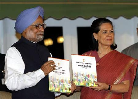 Indian Prime Minister Manmohan Singh (L) and Chief of India's ruling Congress party Sonia Gandhi hold up a recently released book titled ''Report To The People 2010-11'' by the government of United Progressive Alliance (UPA) in New Delhi May 22, 2011. REUTERS/B Mathur/Files