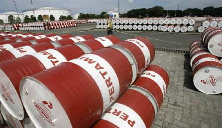 A worker creates a boundary for oil barrels at Pertamina's storage depot in Jakarta January 26, 2011. REUTERS/Supri/Files