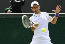 O tenista sérvio Novak Djokovic retorna jogada para o sul-africano Kevin Anderson em partida do campeonato de Wimbledon. 23/06/2011 REUTERS/Suzanne Plunkett