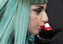 <p>La superestrella del pop Lady Gaga con una muñeca Okiagari-koboshi en Tokio, jun 23 2011. Gaga, que se encuentra en Japón para participar en un concierto benéfico, elogió el jueves al país por su belleza y animó a volver a los turistas, cuyas cifras han caído tras el terremoto, el tsunami y la crisis nuclear. REUTERS/Issei Kato</p>
