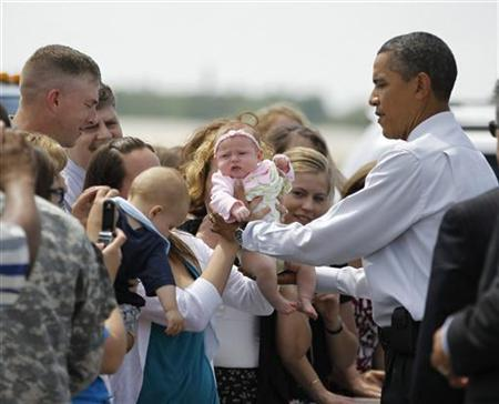 President Barack Obama holds a baby as he greets soldiers and their families during his visit to Fort Drum in New York, June 23, 2011. REUTERS/Jason Reed