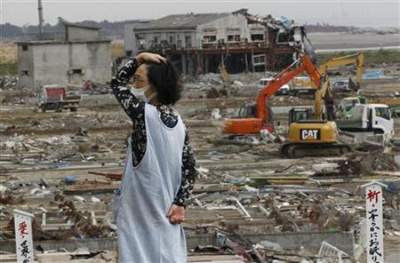 A woman reacts as she looks around a devastated area by March 11th's earthquake and tsunami in Natori, north of Japan, May 21, 2011. REUTERS/Kim Kyung-Hoon