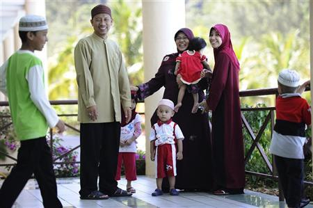 Ishak Md Nor, 40, (2nd L) and his two wives, Aishah Abdul Ghafar, 40, (C) and Afiratul Abidah Mohd Hanan 25, who are members of ''The Obedient Wife Club'', share a light moment with their children after the club's launch in Kuala Lumpur June 4, 2011. REUTERS/Samsul Said