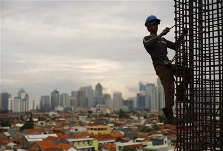 A worker stands on a steel rods at a construction site of Kuningan City superblock in Jakarta February 2, 2010. REUTERS/Beawiharta