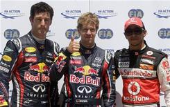 Sebastian Vettel, da Red Bull (centro), comemora o pole position, ao lado de seu companheiro de equipe Mark Webber (esq) e Lewis Hamilton, da McLaren, após sessão classificatória do Grande Prêmio da Europa. 25/06/2011 REUTERS/Albert Gea