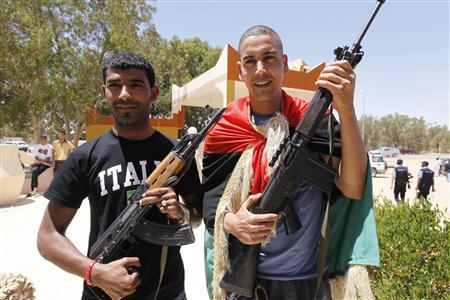 Libyan footballers Owsma Abdul Salam (L) and Juma Gtat pose with rebel weapons in the city of Zintan June 25, 2011. REUTERS/Anis Mili
