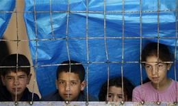 <p>Syrian children look from behind a fence in a refugee camp in the Turkish border town of Yayladagi, in Hatay province, June 26, 2011.REUTERS/Umit Bektas</p>