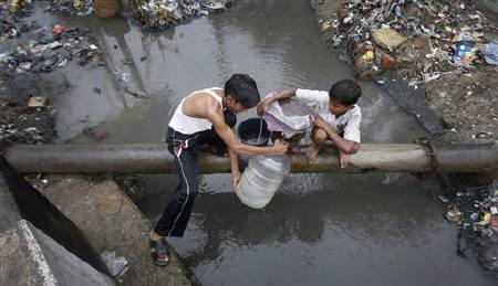 Two boys sit on a water supply pipe over a polluted canal while filling a container with drinking water from a leak in the pipe in Noida June 26, 2011. REUTERS/Parivartan Sharma