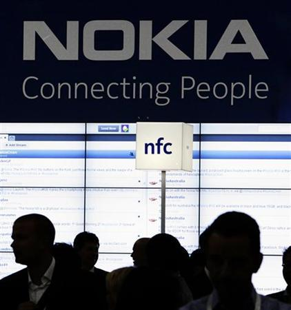 Trade visitors gather at the Nokia booth during the CommunicAsia expo in Singapore June 21, 2011. REUTERS/Tim Chong