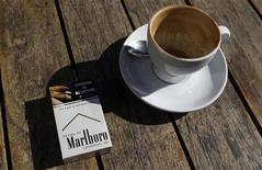 Пачка сигарет Marlboro и чашка кофе в кафе в Сиднее 27 июня 2011 года. Гигант табачной индустрии Philip Morris грозится подать в суд на Австралию, которая первой в мире намерена унифицировать сигаретную упаковку. REUTERS/Daniel Munoz