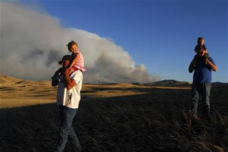 Jason Hill, carrying Peyton Groff (L), and Colt Groff, carrying his son Trayson Groff, look at the smoke from the Wallow wildfire in Apache County, Arizona June 9, 2011. REUTERS/Joshua Lott