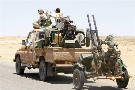 Libyan rebel fighters ride a truck loaded with weapons southeast of Zintan June 28, 2011. REUTERS/Anis Mili