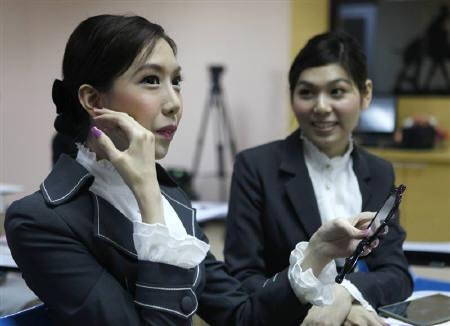 Transsexual flight attendants Nathatai Sukkaset, 26, and Chayathisa Nakmai (L), 24, attend a make-up training session at PC Air office in Bangkok February 9, 2011. REUTERS/Chaiwat Subprasom/Files