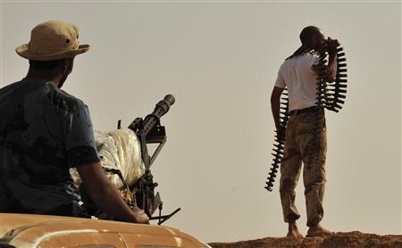 Rebel fighters take up position on the front line, 18 km (11 miles) west of Ajdabiyah, June 27, 2011. REUTERS/Esam Al-Fetori