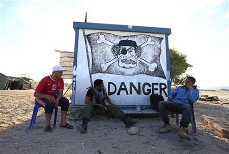 Libyan rebel fighters sit by a caricature of Libya's leader Muammar Gaddafi at a checkpoint west of the rebel-held city of Misrata June 14, 2011. REUTERS/Zohra Bensemra