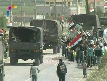 People hold Syrian flags by the side of the road as Syrian military vehicles leave Deraa May 5, 2011 in this still image taken from video. REUTERS/Syrian TV via Reuters TV