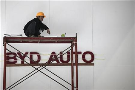 A worker sits in front of the logo of Chinese car manufacturer BYD (Build Your Dreams) Auto, at the World Electric Vehicle Symposium and Exposition (EVS) in the southern Chinese city of Shenzhen November 4, 2010. REUTERS/Tyrone Siu