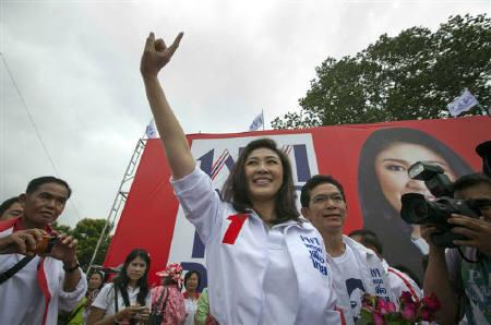 Yingluck Shinawatra, sister of former Thai prime minister Thaksin Shinawatra, raises her hand after taking the stage at a campaign rally in Si Saket, located in northeast Thailand June 29, 2011. Thailand will hold a general election on July 3.    REUTERS/Adrees Latif