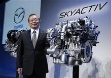 """Глава Mazda Такаси Яманоути показывает двигатель нового поколения """"SKYACTIV"""" на брифинге в Токио, 20 октября 2010 года. Mazda Motor Corp выпустила модифицированную версию субкомпакта Mazda2/Demio, первую модель с новым сверхэкономичным двигателем. REUTERS/Issei Kato"""