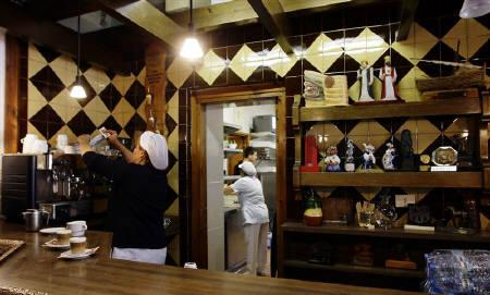 Women work at the snack bar of 'La Masia de Can Planes' in Barcelona, in this October 19, 2009 file photo. REUTERS/Gustau Nacarino/Files