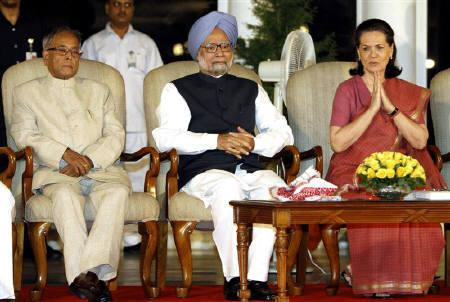 Chief of India's ruling Congress party Sonia Gandhi (R) gestures as Prime Minister Manmohan Singh (C) and Finance Minister Pranab Mukherjee watch during a book release in New Delhi May 22, 2011. REUTERS/B Mathur/Files
