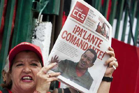 A supporter of Venezuelan President Hugo Chavez, holding a newspaper with a picture of him, attends to a demonstration in Caracas July 1, 2011. REUTERS/Carlos Garcia Rawlins