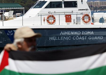 An activist stands in front of a Greek coast guard ship during a demonstration against the Greek authorities' ban on Gaza-bound ships on the Greek island of Corfu July 2, 2011. REUTERS/Marko Djurica