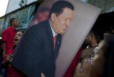 Сторонники президента Венесуэлы Уго Чавеса держат его фотографию во время демонстрации в Каракасе 2 июля 2011 года. Президент Венесуэлы Уго Чавес после лечения рака в Гаване в понедельник прибыл в Международный аэропорт имени Симона Боливара в Майкетии неподалеку от Каракаса, где его приветствовали министры страны, передает государственное телевидение Венесуэлы.   REUTERS/Carlos Garcia Rawlins