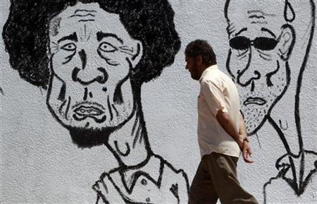 A Libyan man walks past caricatures of Muammar Gaddafi (L) and his son Saif al-Islam near a courthouse in Benghazi June 27, 2011. REUTERS/Amr Abdallah Dalsh