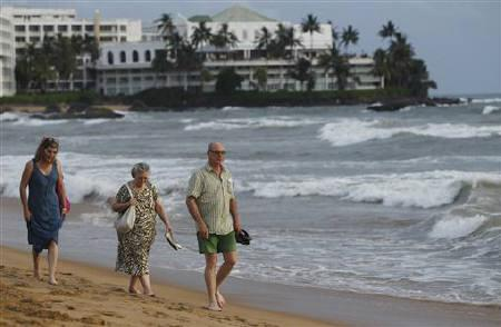 Tourists walk along the Mount Lavinia beach in Colombo June 13, 2011. REUTERS/Dinuka Liyanawatte/Files