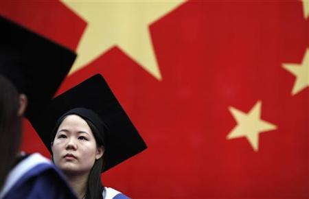 A student listens to a speech during her college graduation ceremony at Fudan University in Shanghai, July 2, 2011. REUTERS/Carlos Barria