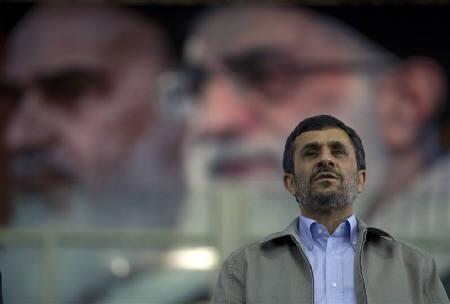 Iran's President Mahmoud Ahmadinejad stands for the national anthem beneath a portrait of Supreme Leader Ayatollah Ali Khamenei during a gathering of reformed drug addicts in Tehran June 26, 2011.  REUTERS/Caren Firouz/Files