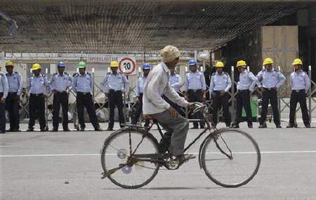 A man rides his bicycle past private security guards standing outside the main entrance to the Maruti Suzuki India Limited plant in Manesar, located in Haryana June 14, 2011. REUTERS/Adnan Abidi/Files