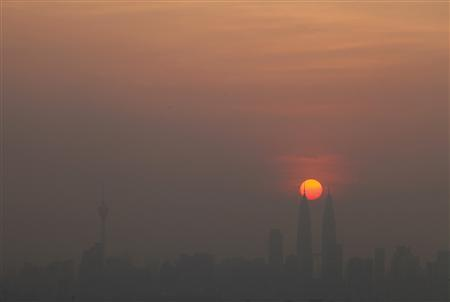 The skyline of Kuala Lumpur is seen covered with smog during sunset in the capital Malaysia July 4, 2011. REUTERS/Bazuki Muhammad