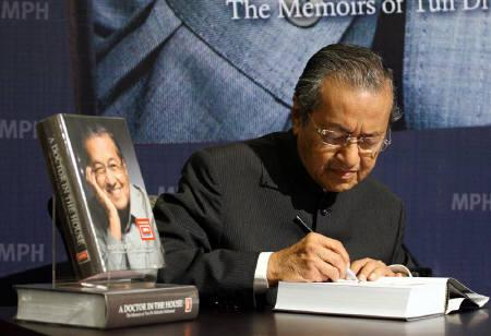 Former Malaysia's Prime Minister Mahathir Mohamad autographs his autobiography in Kuala Lumpur in this March 8, 2011 file photo. REUTERS/Stringer/Files