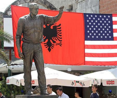 People walk near a statue of former U.S. President George W. Bush unveiled in the centre of the town of Fushe Kruje, some 22 kms (14 miles) from the capital Tirana July 6, 2011. REUTERS/Arben Celi