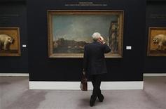 """Мужчина рассматривает картину Франческо Гварди """"Венеция, вид на мост Риальто с набережной дель Карбон"""" в аукционном доме Sotheby's в Лондоне 4 июля 2011 года. Картина Франческо Гварди """"Венеция, вид на мост Риальто с набережной дель Карбон"""" была продана на аукционе Sotheby's за 26,7 миллиона фунтов ($42,9 миллиона) в среду, став самым дорогим произведением искусства, проданным на международном аукционе в этом году.   REUTERS/Suzanne Plunkett"""