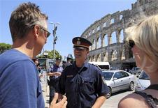 <p>Austrian police officer Johann Zsifkovits talks to tourists during a patrol in Croatia's Adriatic touristic port of Pula, 270 kilometers southwest from capital Zagreb July 4, 2011. REUTERS/Nikola Solic</p>