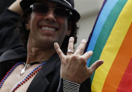 Manuel Rojas shows off his engagement ring during the Gay Pride Parade in New York June 26, 2011. REUTERS/Jessica Rinaldi