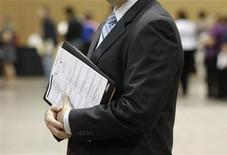 <p>A job seekers holds his binder filled with resumes as he waits in line before speaking with a recruiter during a health care job fair at the Phoenix Convention Center in Phoenix, Arizona November 4, 2009. REUTERS/Joshua Lott</p>