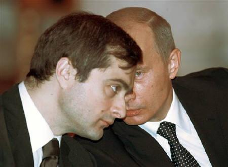 Vladimir Putin (R) talks to aide Vladislav Surkov before a meeting at the Grand Kremlin Palace's St. George's hall in Moscow January 22, 2006. REUTERS/Sergei Karpukhin/Files