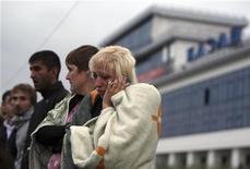 """Женщина, выжившая после затопления теплохода """"Булгария"""", звонит по мобильному телефону, 10 июля 2011 года. Число погибших в результате затопления круизного теплохода на Волге в Татарстане достигло восьми, примерно 100 человек пропали без вести, сообщило местное управление МЧС данные на 8.00 МСК. REUTERS/Roman Kruchinin"""